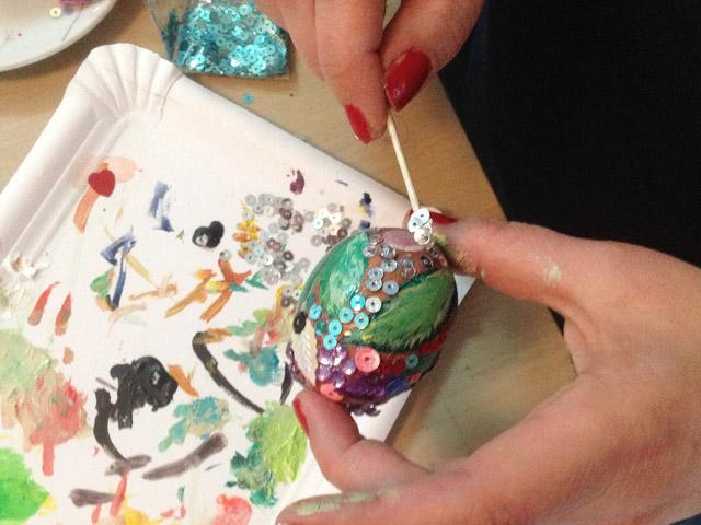 Mica beklebt ein Ei mit Paillietten und Glitter bei Mittelpünktchen