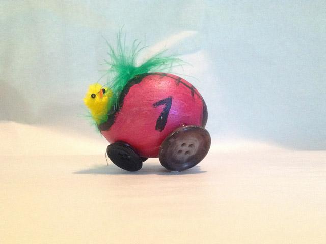 Rennküken sitzt im Rennwagen aus einem zerbrochenen Ei mit Knopfrädern, vom Workshop bei Mittelpünktchen
